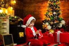 Christmas Kids. Happy little kid is wearing Santa clothes, playing with Christmas gift box. Fireplace background stock image