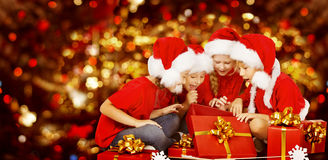 Christmas Kids Opening Present Gift Box, Children in Santa Hat. Christmas Kids Opening Present Gift Box, Happy Children in Santa Hat, Smiling Boys and Girls In Royalty Free Stock Photo