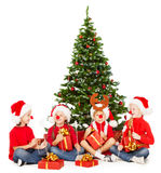 Christmas helpers kids playing under fir tree. New Royalty Free Stock Image