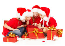 Christmas helpers kids in Santa hat opening gift b Royalty Free Stock Photo