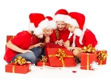 Christmas helpers kids in Santa hat opening gift b