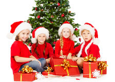 Christmas helpers kids in Santa hat with presents  Stock Photos