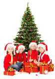 Christmas helpers kids in Santa hat with presents royalty free stock images
