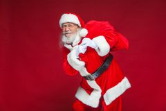 Free Christmas. Kind And Tired Santa Claus In White Gloves Carries A Red Bag With Gifts Over His Shoulder. Isolated On Red Royalty Free Stock Images - 125379099