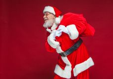 Free Christmas. Kind And Tired Santa Claus In White Gloves Carries A Red Bag With Gifts Over His Shoulder. Isolated On Red Stock Photos - 125807163
