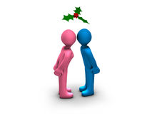 Christmas Kiss. Boy and girl kissing under a mistletoe Royalty Free Stock Image