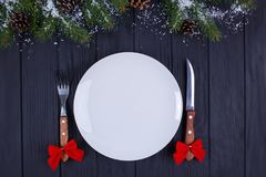 Christmas kitchen, festive dinner, holiday foods. Empty plate wi. Th cutlery decorated with fir tree branches on black wooden background, copy space stock photo