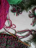 Christmas knitting. In vibrant colors on white wooden background Royalty Free Stock Image
