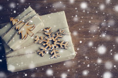 Christmas Kraft Boxes with Gifts Decorated in Rustic Style on Wooden Background. Vintage Image with Drawn Snowfall. Royalty Free Stock Photos