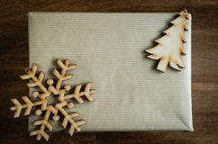Christmas Kraft Gift Box in Rustic Style Decorated with Wooden Snowflake and Christmas Tree on Wooden Background. Stock Photography