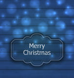 Christmas label on wooden texture with light Stock Photos