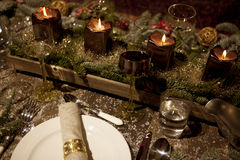 Christmas laid table in the candlelight. Christmas place setting with candles, are wine glasses on the table, pine tree branches are adorned with decorative snow Stock Images