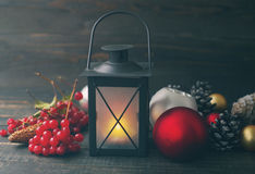 Christmas lamp and glass spheres with cones on a wooden background. Royalty Free Stock Photography