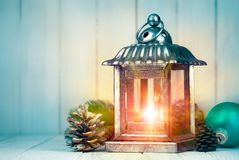 Christmas lamp with pinecone and ball on wooden board Royalty Free Stock Photography