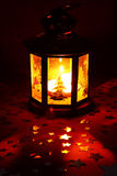 Christmas lantern. Glowing in dark with silver stars on red background Stock Photos