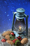 Christmas Lantern. Lit lantern with christmas objects on a blue snow effect background Stock Image