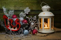 Christmas lantern and balls in a sled by a wooden wall.   New Year`s composition. stock images