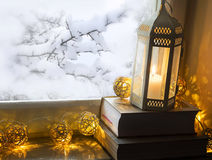 Christmas lantern with books and lights on frozen window backgro Stock Photos