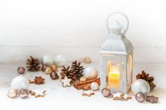 Christmas lantern with burning candle light and decoration like. Baubles, pine cones and cinnamon star cookies on rustic white wood with copy space, selected Royalty Free Stock Images
