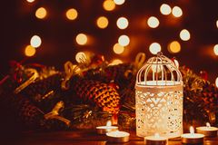 Christmas lantern with burning candles and garland on vintage wooden table Stock Photo