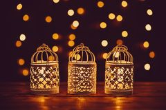Christmas lantern with burning candles and garland on vintage wooden table with golden bokeh. Free space Royalty Free Stock Image