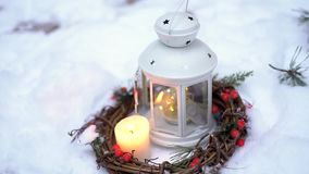 Christmas lantern with candle. It stands in the snow stock video footage