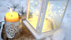 Christmas lantern with candle. It stands in the snow. Clouse up stock video