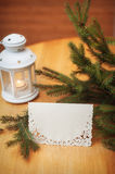 Christmas lantern with fir and snow on vintage wooden background Stock Image