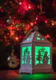 Christmas lantern green light. Green light reflected on a dark table from a little white wooden lantern with stars, Christmas trees, snow crystals and snowmen in royalty free stock photos