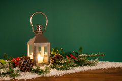 Christmas lantern hooly and snow green background Stock Images