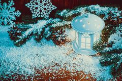 Christmas lantern with lit by candles, Christmas tree branches, cones, snowflakes and snow. On vintage wooden background Royalty Free Stock Photo
