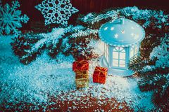 Christmas lantern with lit by candles, Christmas tree branches, cones, snowflakes and snow. Christmas lantern with lit by candles, Christmas tree branches, gift Stock Photos