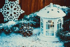 Christmas lantern with lit by candles, Christmas tree branches, cones, snowflakes and snow on vintage wooden background. Free space Royalty Free Stock Image