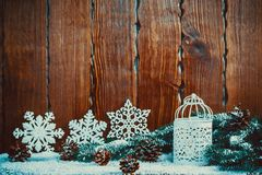 Christmas lantern with lit by candles, Christmas tree branches, cones, snowflakes and snow on vintage wooden background. Free space Stock Images