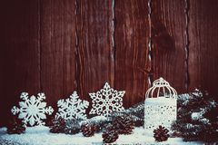 Christmas lantern with lit by candles, Christmas tree branches, cones, snowflakes and snow on vintage wooden background. Free space Royalty Free Stock Photos