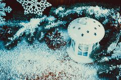 Christmas lantern with lit by candles, Christmas tree branches, cones, snowflakes and snow. On vintage wooden background. Free space Royalty Free Stock Image