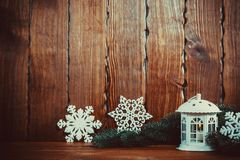 Christmas lantern with lit by candles Christmas tree branches, and snowflakes on vintage wooden background. Free space Royalty Free Stock Photo