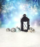 Christmas lantern with ornaments. Christmas lantern and ornaments on the snow in a blue shinning night Stock Images