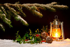Christmas lantern scene. Christmas scene - an oil filled lantern burning bright with snow covered tree, holly and ivy lit up by the glow of the lamp stock photo