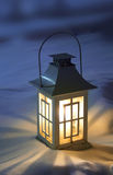 Christmas lantern on snow. White christmas lantern with candle inside, on pure snow, in evening light stock photos