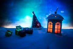 New Year's still-life postcard red lamp candle wax-boxes gift-box Christmas tree light bulbs lights wooden background snow. Christmas lantern on snow with gifts stock image