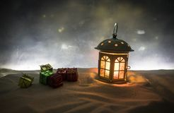 New Year's still-life postcard red lamp candle wax-boxes gift-box Christmas tree light bulbs lights wooden background snow. Christmas lantern on snow with gifts stock photo