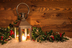Christmas lantern in snow and holly Stock Image