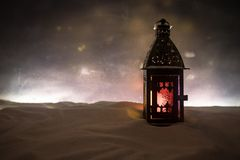 New Year's still-life postcard red lamp candle wax-boxes gift-box Christmas tree light bulbs lights wooden background snow. Christmas lantern on snow at night royalty free stock images