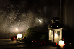 Christmas lantern with snowfall, candles, view from the window on the night street Stock Photos