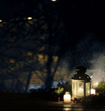 Christmas lantern with snowfall, candles, view from the window on the night street Royalty Free Stock Photo