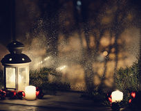 Christmas lantern with snowfall, candles, view from the window on the night street Royalty Free Stock Photography