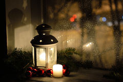 Christmas lantern with snowfall, candles, view from the window on the night street Royalty Free Stock Images