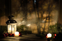 Christmas lantern with snowfall, candles, view from the window on the night street Stock Images