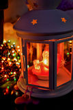 Christmas lantern with wax running down with burning candle on the background of garlands Royalty Free Stock Images